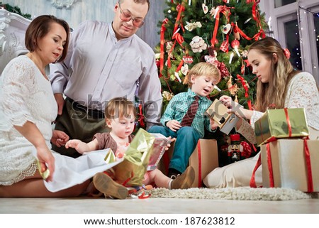Mother, father and three children examine content of gift boxes under Christmas tree, low angle view