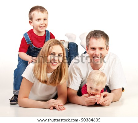 Mother, father and two children lying on the floor - stock photo