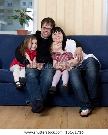 Mother, father and two daughters rest on sofa at home