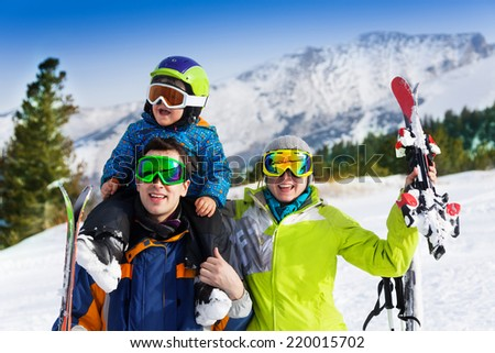 Mother, father with child on his shoulders in ski masks holding ski on mountains background - stock photo