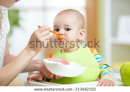 Mother feeding baby girl. Child sitting in hich chair in kitchen. - stock photo