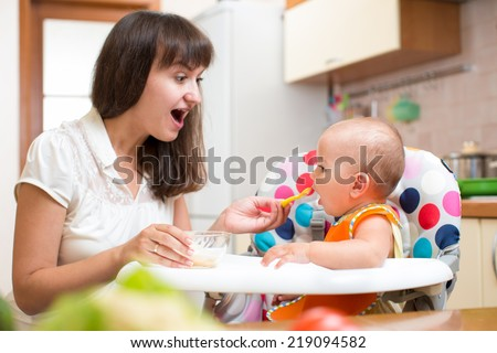 Mother feeding baby with spoon - stock photo
