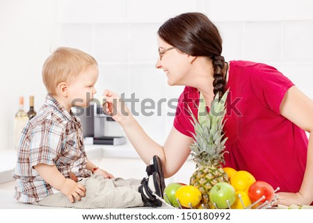 Mother feeding child with an apple in the kitchen - stock photo