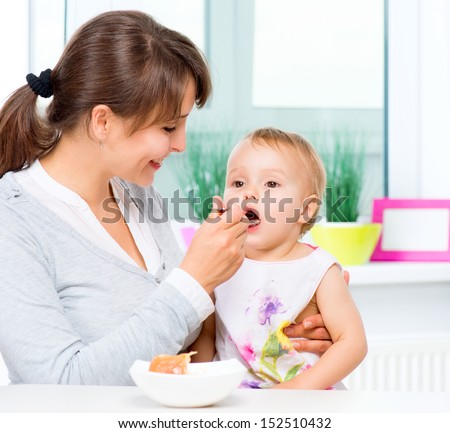 Mother Feeding Her Baby Girl with a Spoon. Mother Giving Food to her adorable Child at Home