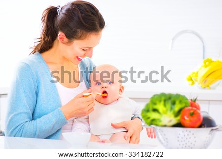 Mother Feeding Her Baby Girl with a Spoon. Mother Giving Food to her adorable Child at Home. Baby food, diet - stock photo