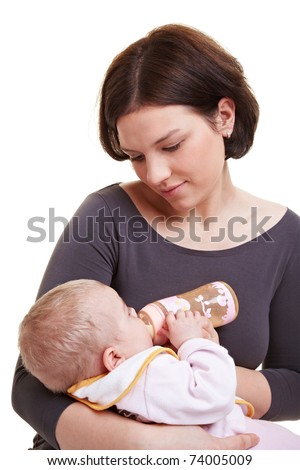 Mother feeding her baby girl with milk from a bottle - stock photo