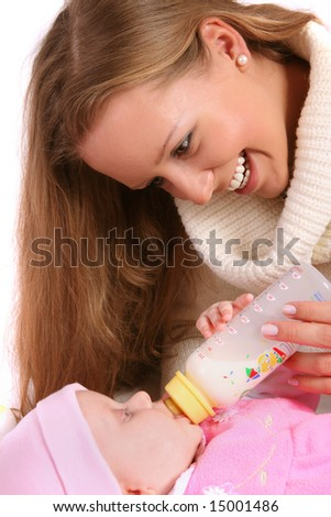 mother feeding her child with bottle of milk - stock photo
