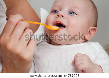 Mother feeding her 5 month old son with spoon