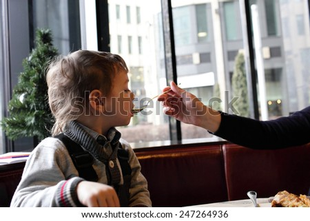 Mother feeding her son in the restaurant - stock photo