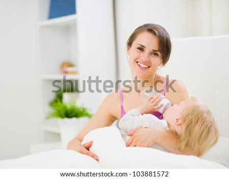 Mother feeding kid in bed - stock photo