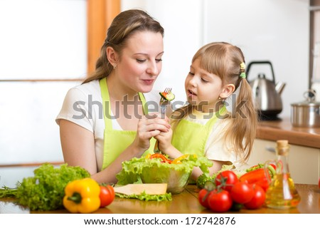 mother feeding kid vegetables in kitchen - stock photo