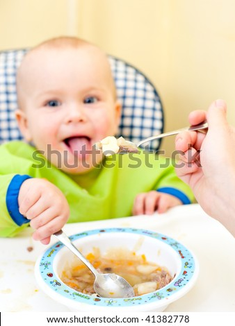 Mother feeding little baby girl in a highchair, focus on spoon with food - stock photo