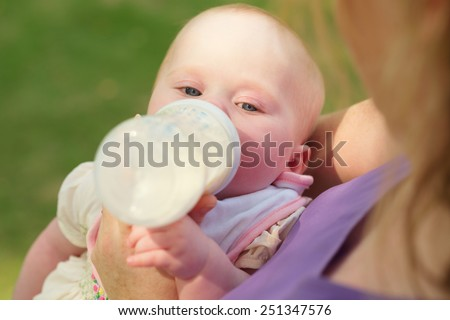 Mother feeding newborn daughter from a bottle - stock photo