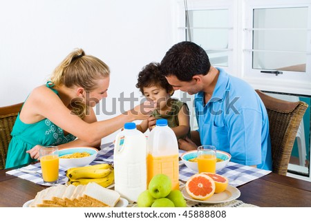 mother feeding toddler boy healthy breakfast at home - stock photo
