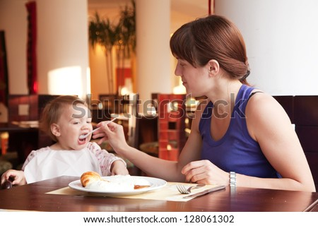Mother feeding  year-old  daughter with spoon