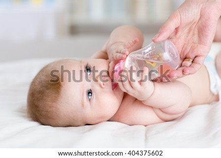 Mother feeds baby daughter bottle in nursery - stock photo