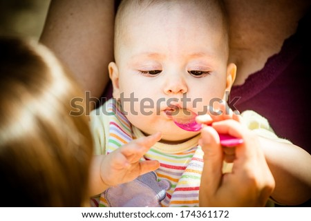 Mother feeds her baby with spoon, close-up on face - stock photo