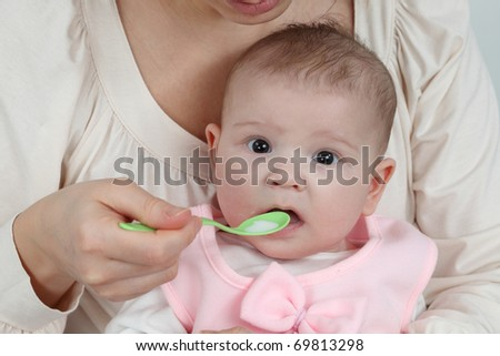 Mother feeds her little baby with spoon - stock photo