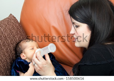 Mother feeds her newborn infant feeds on a bottle of baby formula. - stock photo