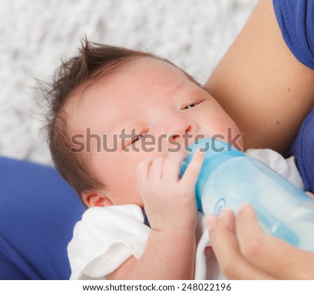 mother feeds the baby bottle - stock photo