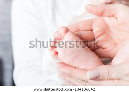 Mother gently holding her babys foot - stock photo