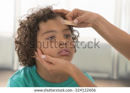 mother  getting plaster to child's wound.