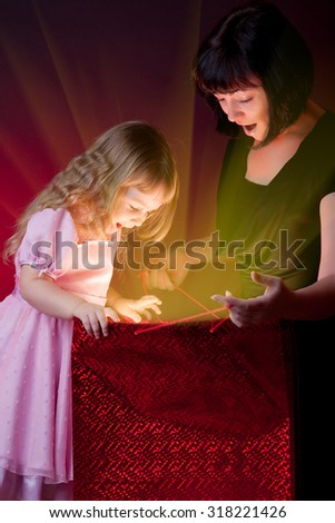 Mother give gift to her little daughter - stock photo