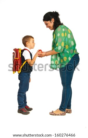 Mother giving apple to her son and prepare for school - stock photo