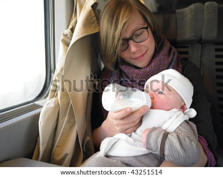 Mother giving baby a bottle while traveling on a train. Horizontally framed shot. - stock photo