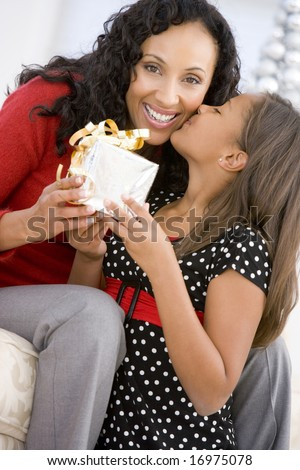 Mother Giving Daughter Her Christmas Present - stock photo