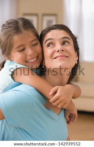 Mother giving daughter piggy back ride - stock photo