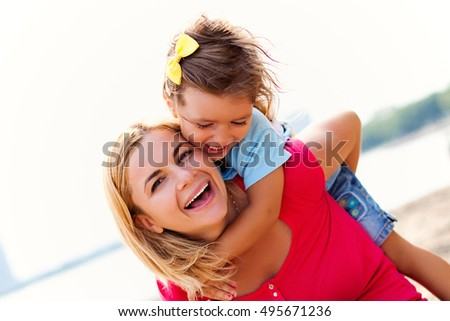 Mother giving daughter piggyback ride outside