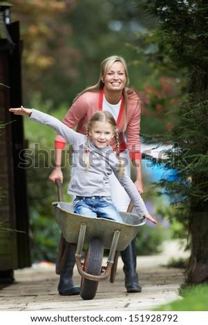 Mother Giving Daughter Ride In Wheelbarrow - stock photo
