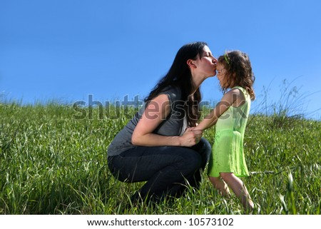 Mother giving her daughter a kiss in a meadow - stock photo