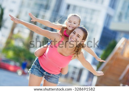 Mother Giving Her Daughter A Piggy Back Ride. A Young girl hugging her mother piggyback style. childhood and parenting concept - happy mother and child doing piggy back