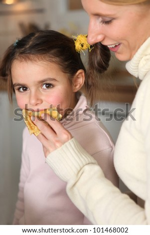 Mother giving her daughter a snack - stock photo