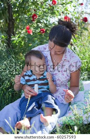Mother giving homeopathic medicine to her son. Shallow DOF, focus is on their faces. - stock photo