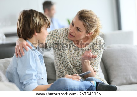 Mother giving warning to young boy using smartphone - stock photo