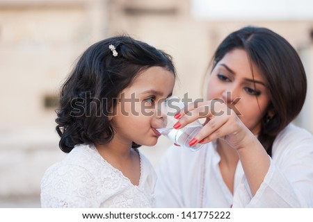 mother giving water to little daughter, indian mother and daughter - stock photo