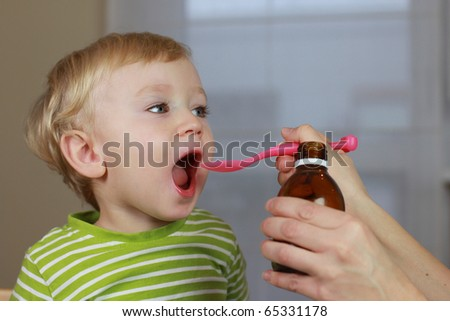 Mother giving 2 years old baby boy medicine, cough syrup on a spoon. Sick child. - stock photo