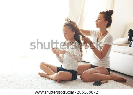 Mother hairdressing her preteen daughter at home - stock photo