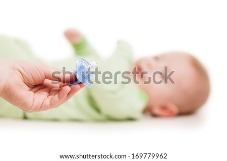 Mother hand giving plastic soother pacifier to little cute sleeping newborn baby child white isolated - stock photo