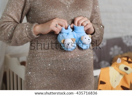 Mother Hand Holding Newborn Baby Booties,  New Born Boy - stock photo