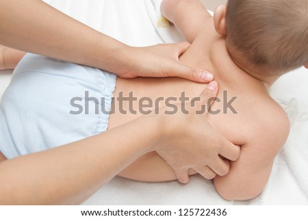 Mother hand massaging back muscle  of her baby,touch of Happiness - stock photo