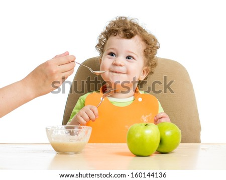 mother hand spoon feeding baby boy - stock photo