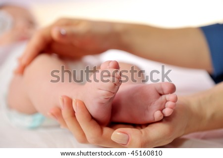 mother hands holding tiny baby feet