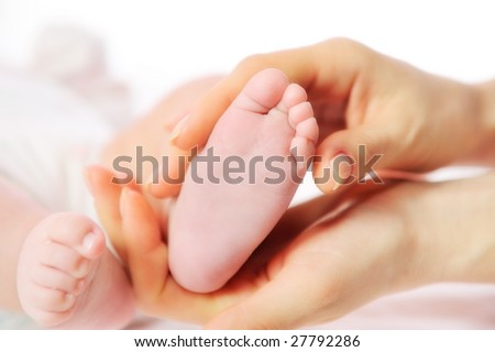 mother hands holding tiny baby foot