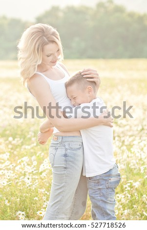 Mother having fun with his son in the blossom field of camomile in Crimea region
