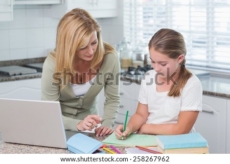 Mother helping daughter doing homework at home in the kitchen - stock photo