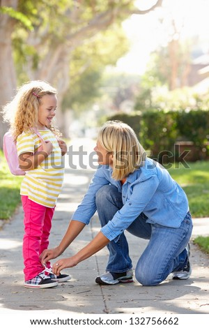 Mother Helping Daughter Tie Shoe Laces On Walk To School - stock photo